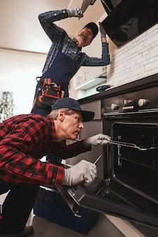 Foto produttiva insieme di due meccanici che lavorano in cucina