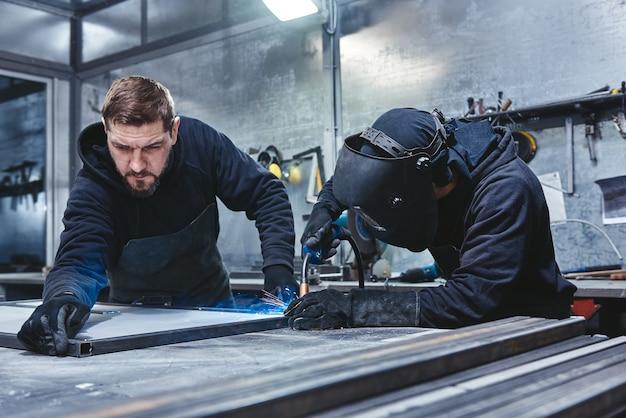 Saldatore professionale in uniforme protettiva e struttura metallica per saldatura maschera sul tavolo industriale