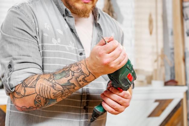 Professione, carpenteria, lavorazione del legno e concetto di persone, il carpentiere prepara il trapano per il lavoro