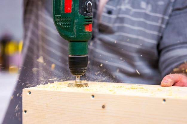 Professione, carpenteria, lavorazione del legno e concetto della gente - carpentiere con il trapano elettrico che perfora la plancia di legno all'officina