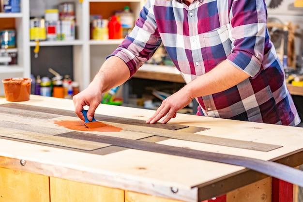 Professione, carpenteria, lavorazione del legno e concetto della gente - carpentiere che lavora con la plancia di legno