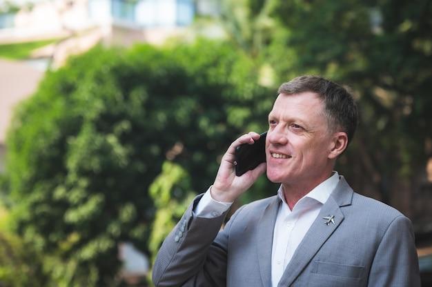 Imprenditore adulto professionale parlando con lo smartphone