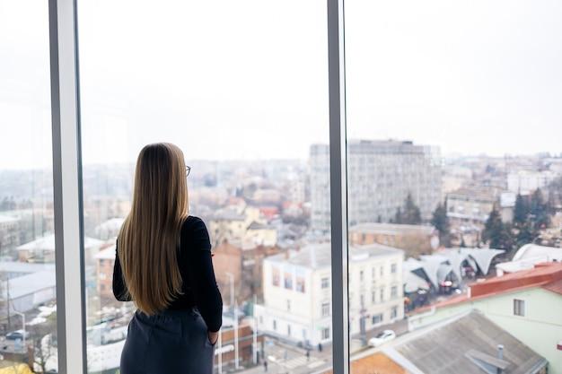 Donna d'affari adulta professionista impegnata a mandare sms sul suo telefono cellulare indossando camicia e pantaloni in piedi davanti a grandi finestre di vetro.