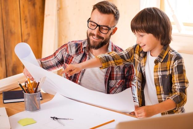 Consigli professionali dalla visione del bambino. giovane allegro che tiene il progetto mentre suo figlio lo indica