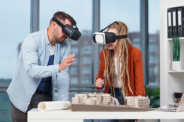 Architetto professionista che lavora alla scrivania dell'ufficio e indossa un auricolare vr, sta visualizzando un'interfaccia di realtà virtuale