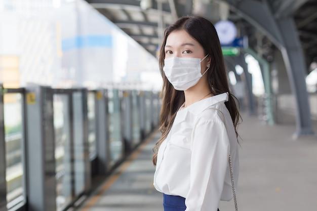 Una donna d'affari asiatica professionista con i capelli lunghi indossa una maschera in attesa di andare al posto di lavoro