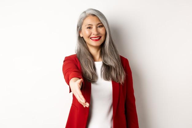 Donna d'affari asiatica professionale con i capelli grigi, salutando, allungando la mano per la stretta di mano e sorridendo, in piedi su sfondo bianco