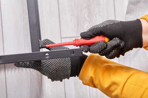 L'assemblatore professionista assembla mobili imballati in piano iniziando con l'assemblaggio del telaio metallico utilizzando un cacciavite.