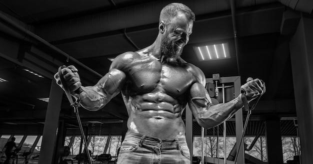 Atleta professionista si allena con elastici in palestra. concetto di bodybuilding e fitness. tecnica mista