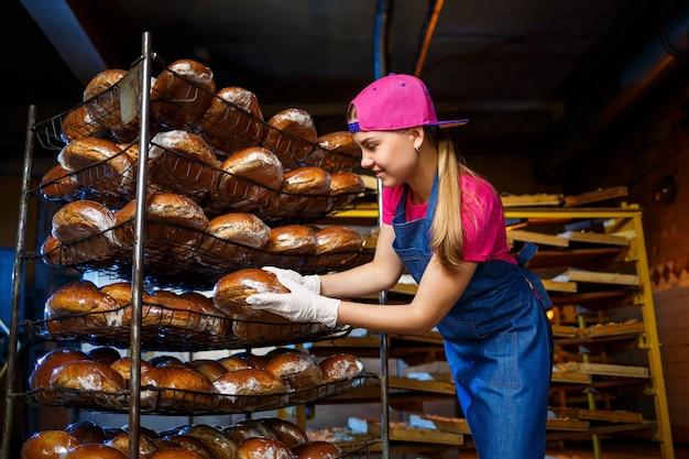 Fornaio professionista - una donna giovane e carina in un grembiule di jeans tiene il pane fresco sullo sfondo di una panetteria o di una panetteria. prodotti da forno. produzione di pane