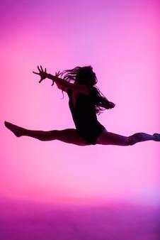 Ballerina professionista che balla balletto in un fumo. donna in tuta nera su sfondo di proiettori.