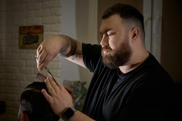 Barbiere professionista che fa acconciatura al suo cliente nel negozio di barbiere