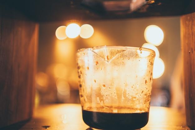 Il barista professionista prepara una bevanda fresca con tè e latte in tazza, bevanda gustosa bar caffetteria, mano che tiene il latte latte in caffetteria o ristorante di cibo, barista che lavora in uniforme da caffetteria