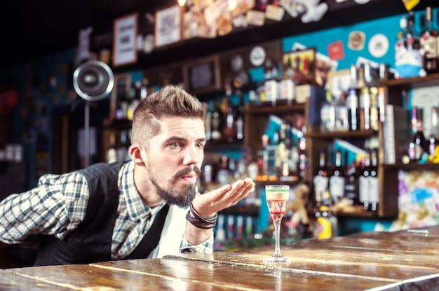 Il barista professionista termina intensamente la sua creazione al night club