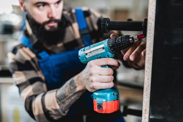 Carpentiere barbuto professionista che lavora nella sua officina, lavorazione del legno e concetto di artigianato.