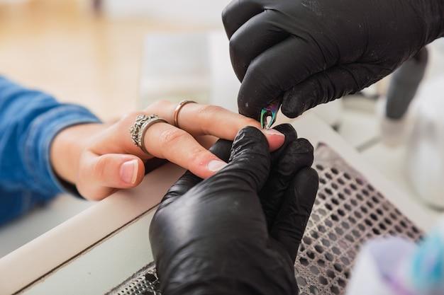 L'estetista professionista taglia le cuticole del cliente