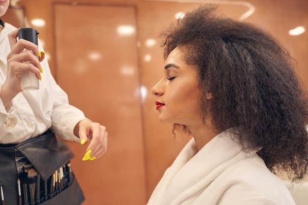 Artista di bellezza professionista che applica con cura lo spray per il viso mentre la cliente femminile calma tenendo gli occhi chiusi