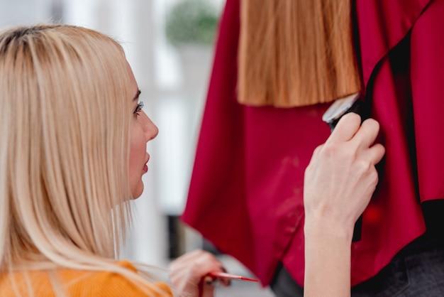 Il parrucchiere professionista della donna bionda taglia i capelli lunghi del cliente usando il tagliatore di capelli