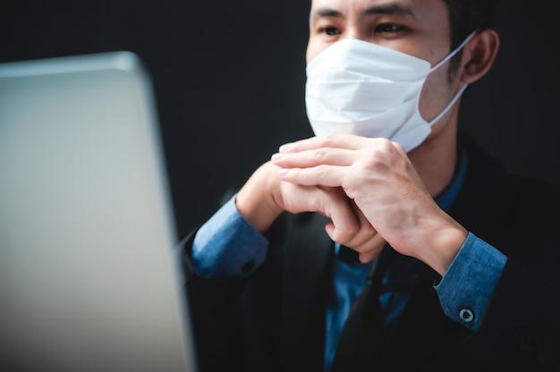 Uomo d'affari professionale che lavora con computer labtop durante la quarantena domestica della pandemia del virus corona flu tramite maschera chirurgica