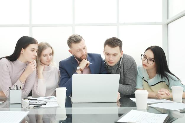 Il team aziendale professionale guarda da vicino lo schermo del laptop