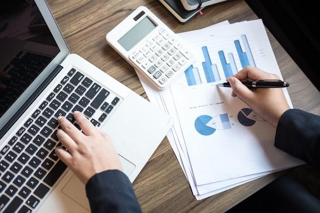 Donna professionale di affari che lavora con il calcolatore, facendo finanza sul computer portatile