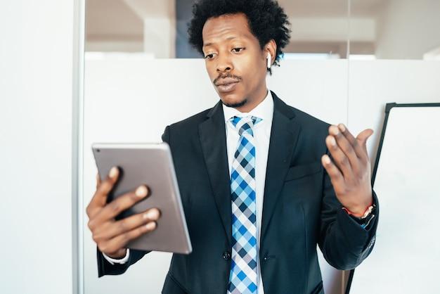 Imprenditore professionista in una riunione virtuale in videochiamata con tavoletta digitale in ufficio. concetto di affari.