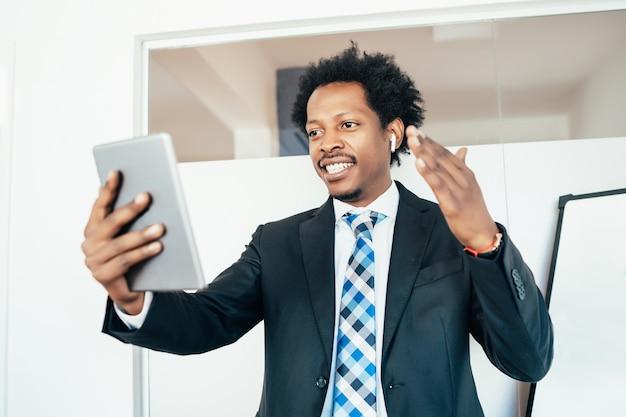 Imprenditore professionista in una riunione virtuale in videochiamata con tavoletta digitale in ufficio