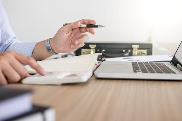 Uomo d'affari professionale che lavora al posto di lavoro con relazione, facendo finanza sul portatile