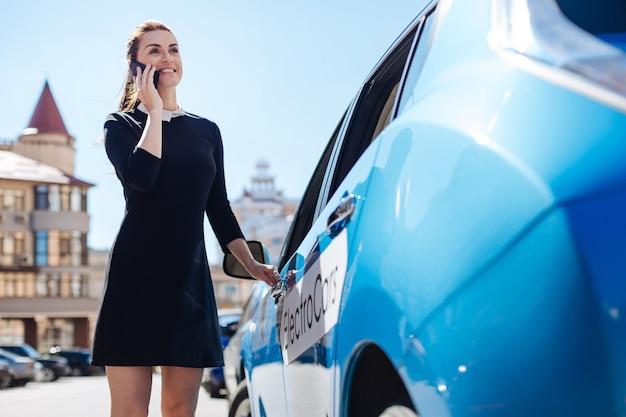 Imprenditrice professionale. donna di affari attraente piacevole contentissima che parla sul telefono e che sorride mentre apre la sua automobile