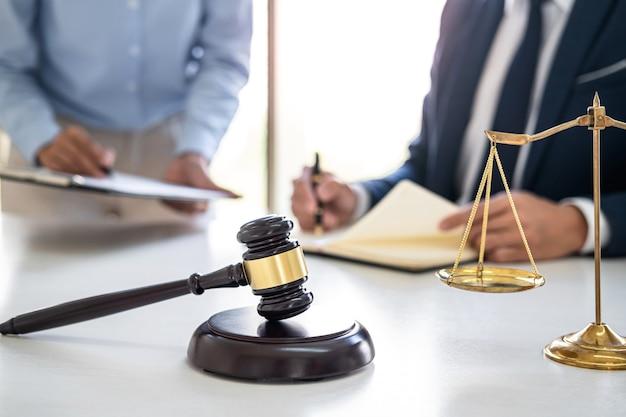 Donna d'affari professionista e avvocati maschi che lavorano e discutono presso uno studio legale in ufficio