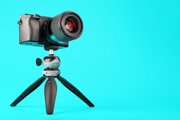 Fotocamera professionale su un treppiede, su un blu. registra video e foto per il tuo blog o rapporto.