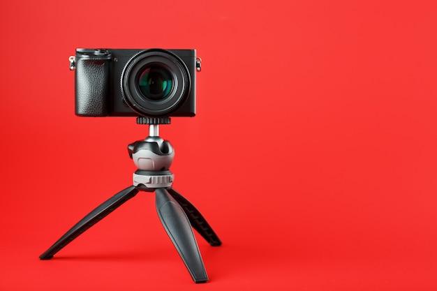 Fotocamera professionale su un treppiede, su uno sfondo rosso. registra video e foto per il tuo blog, reportage