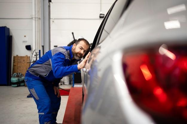 Meccanico di automobile professionista che controlla la carrozzeria del veicolo in officina.
