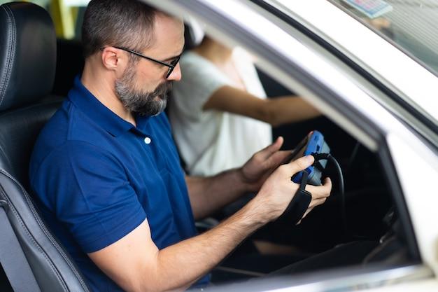Servizio di riparazione meccanico professionale e controllo del motore dell'auto dal computer del software diagnostico. esperto meccanico che lavora nel garage di riparazione di automobili.