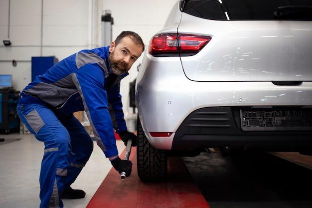 Meccanico automobilistico professionista che lavora nell'officina del veicolo per la manutenzione e la manutenzione di automobili.