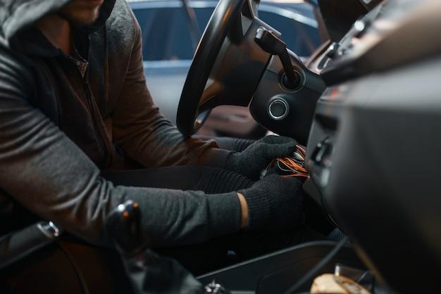 Ladro di auto professionale hacking blocco dell'accensione, stile di vita criminale. ladro maschio incappucciato rompe il sistema di sicurezza del veicolo sul parcheggio. rapina automobilistica, crimine automobilistico