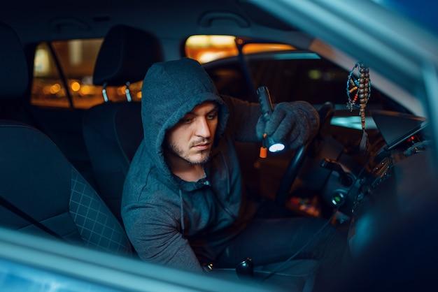 Ladro di auto professionale con torcia elettrica, stile di vita criminale, furto.