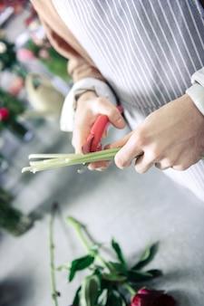 Assistenza professionale. fiorista competente in piedi sul posto di lavoro e prepara i fiori per la vendita