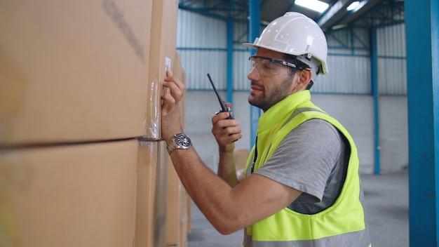 Il lavoratore professionista del carico parla alla radio portatile per contattare un altro lavoratore. concetto di comunicazione di fabbrica e magazzino.