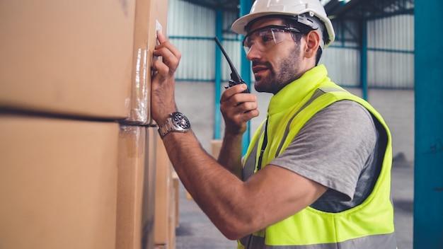 Il lavoratore professionista del carico parla alla radio portatile per contattare un altro lavoratore