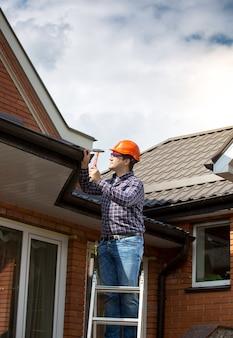 Carpentiere professionista in piedi su una scala alta e riparare il tetto della casa