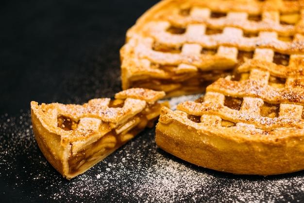 Ristorazione professionale. primo piano della torta di mele con cannella cosparsa di zucchero in polvere.