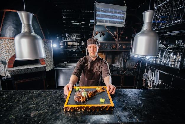 Uno chef professionista serve splendidamente una succosa bistecca alla griglia con burro e condimenti