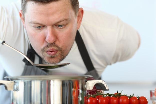 Chef professionista che soffia mestolo di minestra. blog culinario a casa.