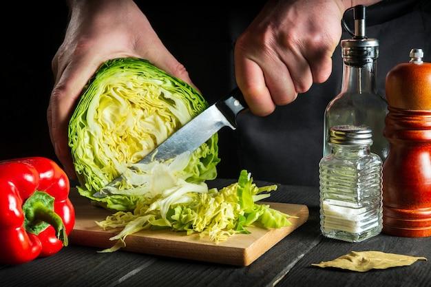 Cuoco unico professionista o mani del cuoco che affettano il cavolo con un primo piano del coltello. cucinare insalata di verdure nella cucina del ristorante