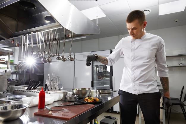 Chef professionista che cucina nella cucina moderna nel ristorante dell'hotel che prepara insalata di gamberetti
