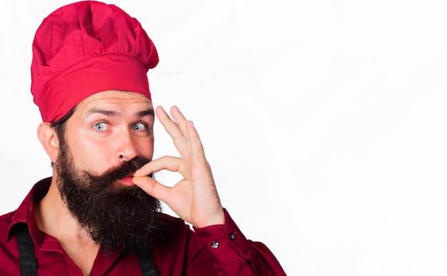 Uomo chef professionista che mostra il segno per delizioso. cuoco in uniforme con segno perfetto. fornaio barbuto con gesto di approvazione del gusto.