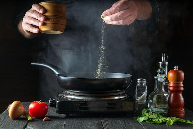 Lo chef professionista versa le spezie nella padella