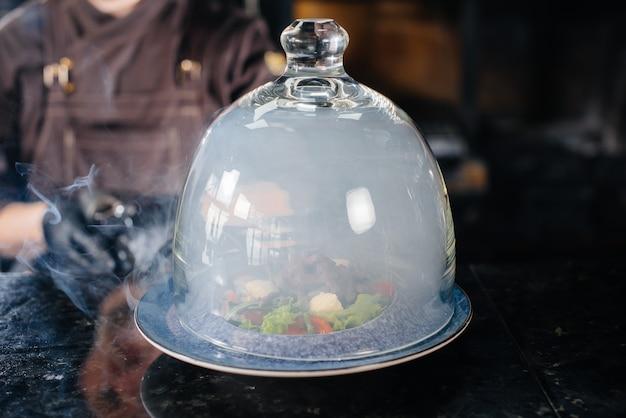 Uno chef professionista serve un'insalata appena preparata di pomodori e verdure di vitello sotto una cappa di vetro con un fumo denso. bellissimo servizio affumicato nel ristorante.