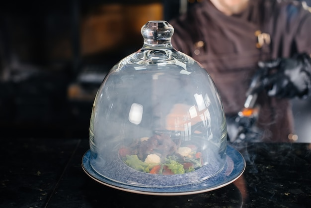 Uno chef professionista serve un'insalata appena preparata di pomodori e verdure di vitello sotto una cappa di vetro con fumo denso